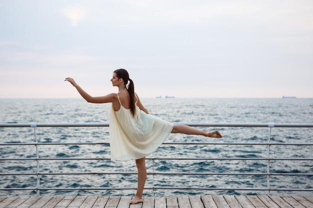 Joven hermosa bailarina bailando y posando afuera Foto gratis