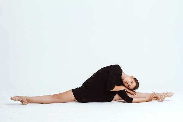 Joven hermosa bailarina contemporánea posando sobre la pared blanca. copia espacio Foto gratis