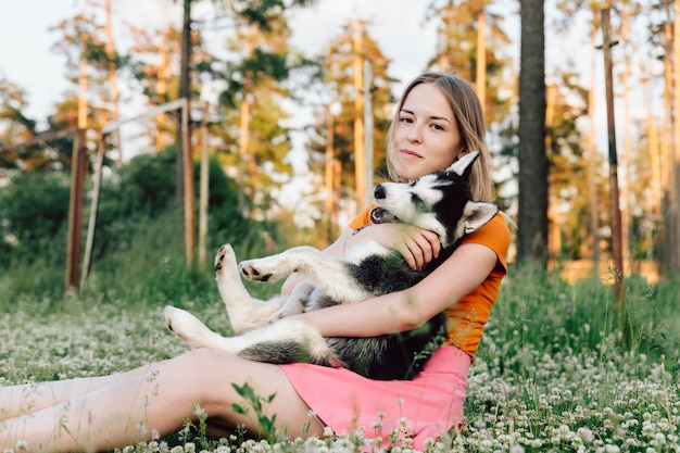 Una joven hermosa con cabello rubio está sentada en un claro con su mascota cachorro husky y abrazándolo. Foto Premium