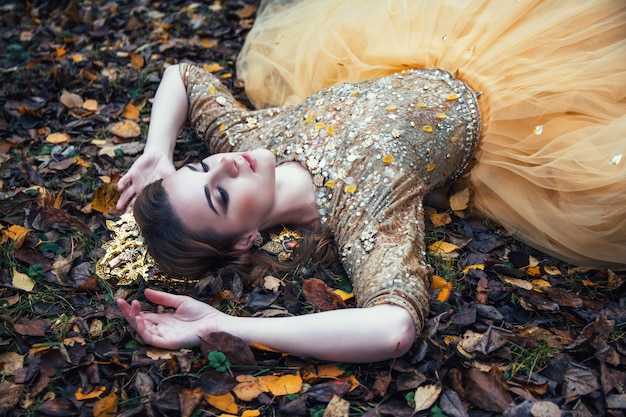 Joven hermosa chica sexy en vestido de oro en el bosque de otoño Foto Premium