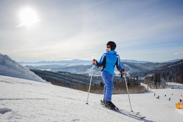 Joven hermosa esquiador femenino en medio de la pista de esquí mirando al sol Foto Premium