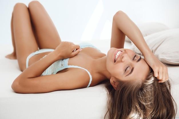 Joven hermosa mujer acostada en la cama temprano en la mañana Foto gratis