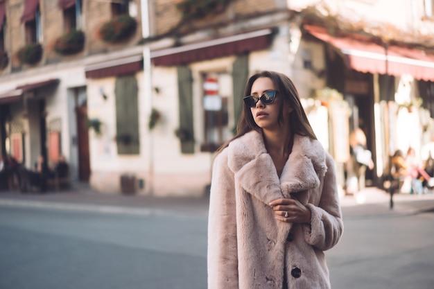 Joven hermosa mujer elegante caminando en abrigo rosa Foto gratis