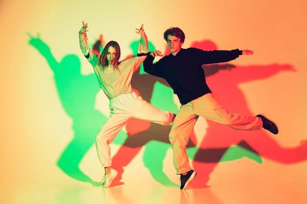 Joven hermosa mujer y hombre bailando hip-hop, estilo callejero aislado en estudio Foto gratis