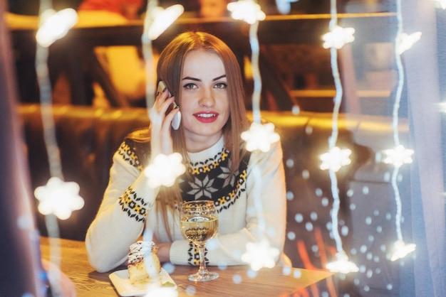 Joven hermosa mujer sentada en la cafetería, bebiendo vino. navidad, año nuevo, día de san valentín, vacaciones de invierno Foto Premium