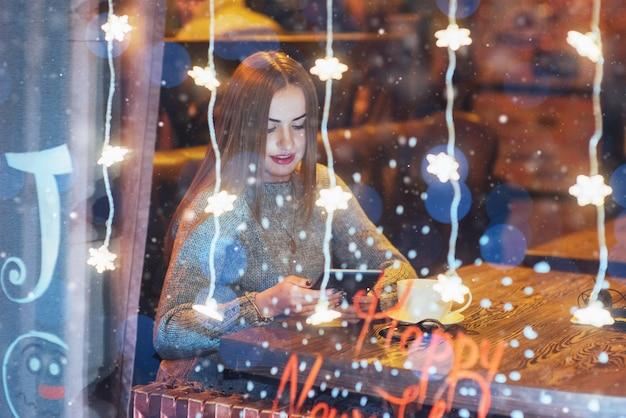 Joven hermosa mujer sentada en la cafetería, tomando café. Foto Premium