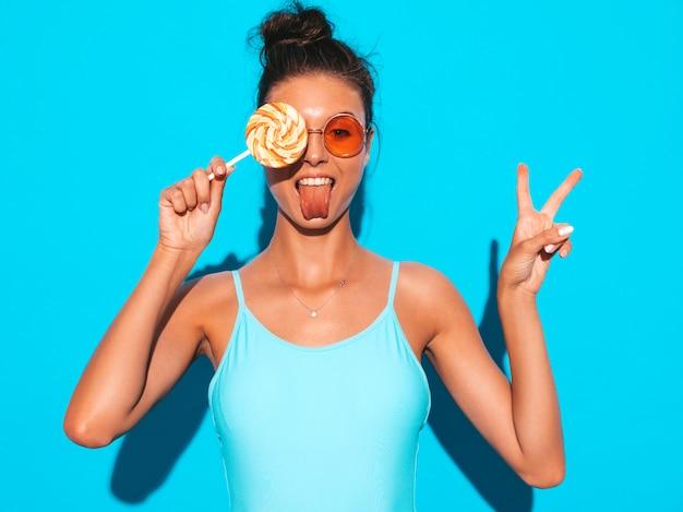 Joven hermosa mujer sexy hipster con labios rojos en gafas de sol. chica de moda en ropa de baño de verano. hembra positiva volviéndose loca modelo divertido aislado en azul comer paleta de caramelo Foto gratis