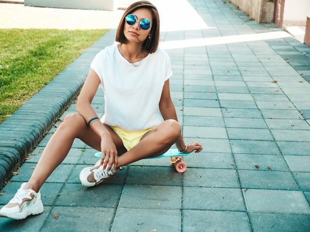 Joven hermosa mujer sexy hipster sonriente en gafas de sol. chica de moda en camiseta y pantalones cortos de verano. mujer positiva con patín azul centavo posando en el fondo de la calle Foto gratis