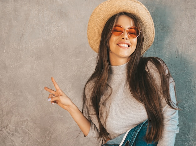 Joven hermosa mujer sonriente mirando. chica de moda en ropa de verano casual monos y sombrero. muestra signo de paz Foto gratis