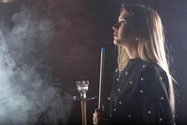 Joven, hermosa niña fuma una cachimba Foto Premium