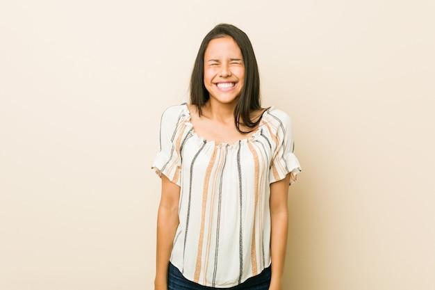 La joven hispana se ríe y cierra los ojos, se siente relajada y feliz. Foto Premium