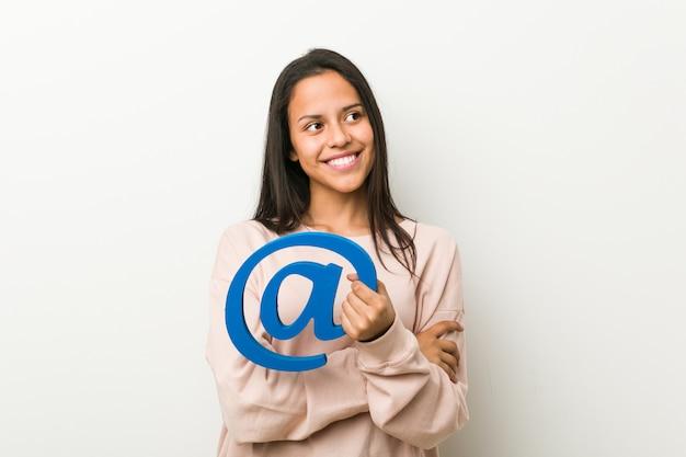 Joven hispana sosteniendo un icono en sonriendo confiado con los brazos cruzados. Foto Premium
