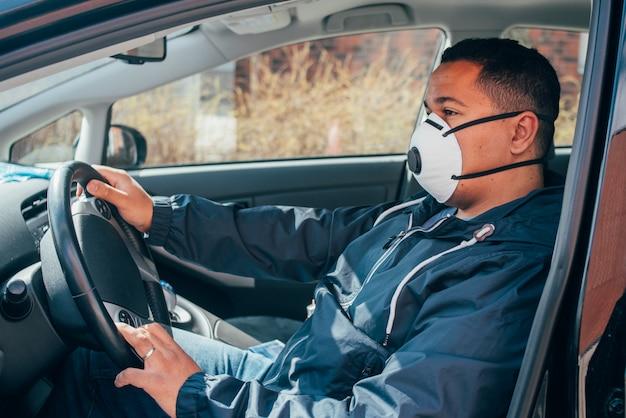 El joven hispano que está en el automóvil usa una máscara protectora para prevenir la propagación del coronavirus. Foto Premium
