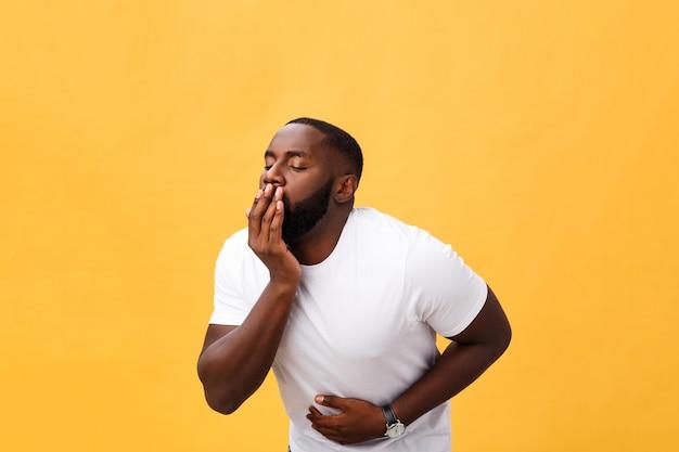 Joven hombre afroamericano con camiseta blanca con la mano en el estómago porque náuseas Foto Premium