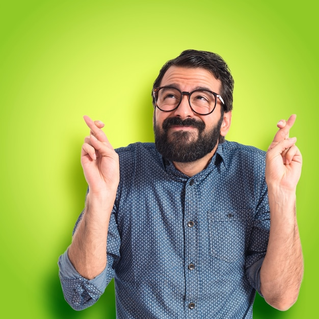 345f2b28e522b Joven hombre de moda con sus dedos cruzando sobre fondo de colores ...