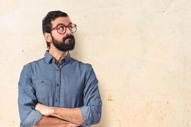 Joven hombre hipster pensando sobre fondo blanco Foto gratis