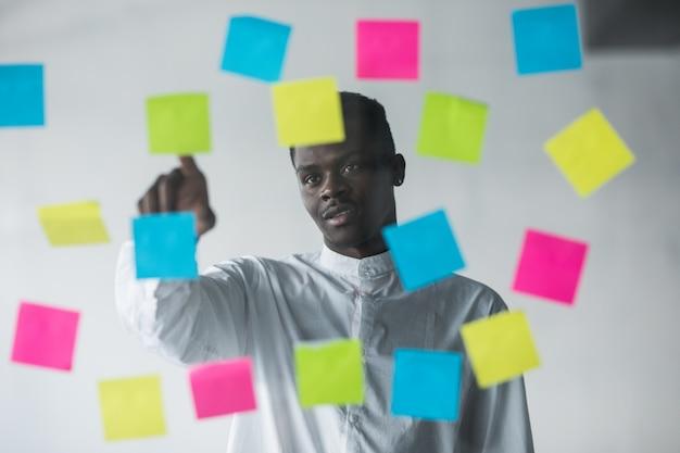 Joven hombre de negocios de pie delante de pegatinas de pared de vidrio y puntiagudo, elija la pegatina derecha en su oficina Foto gratis