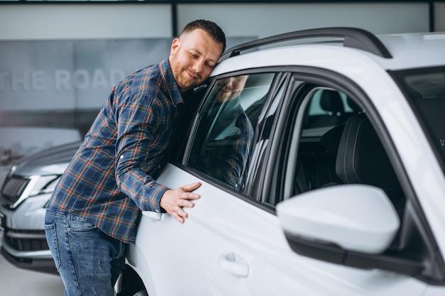 Joven huggingf un automóvil en una sala de exposición de automóviles Foto gratis