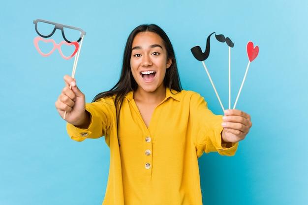 Joven india divirtiéndose y sosteniendo una fiesta objetos aislados Foto Premium