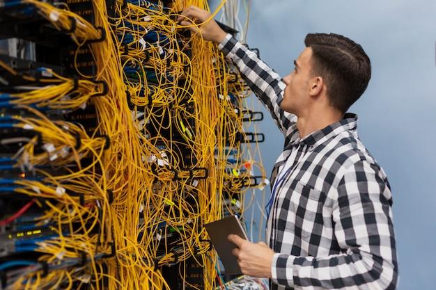 Joven ingeniero de redes trabajando en una sala de servidores Foto gratis