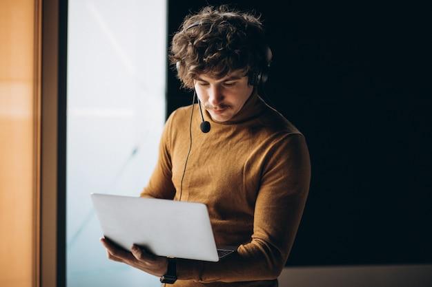 Joven intérprete masculino trabajando en la computadora portátil Foto gratis