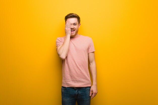 Joven jefe gritando feliz y cubriéndose la cara con la mano Foto Premium