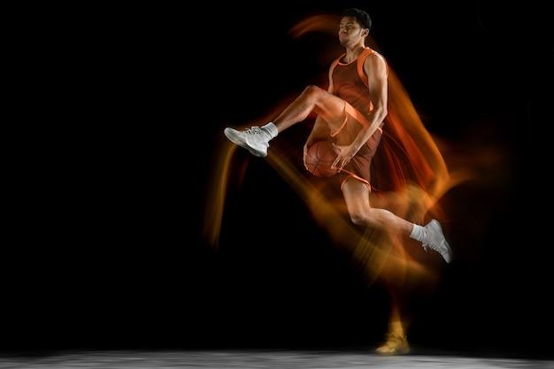 Joven jugador de baloncesto árabe musculoso en acción, movimiento aislado en negro Foto gratis