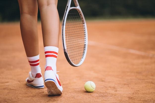 Joven jugadora de tenis en la cancha, pies de cerca Foto gratis