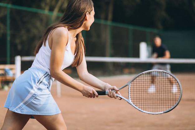 Joven jugando al tenis en la cancha Foto gratis