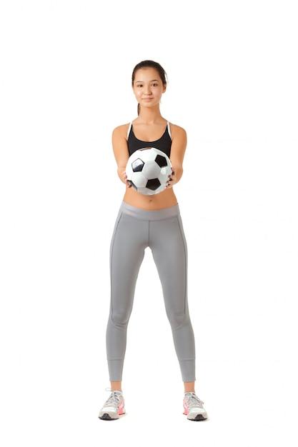 Joven jugando con un balón de fútbol Foto Premium