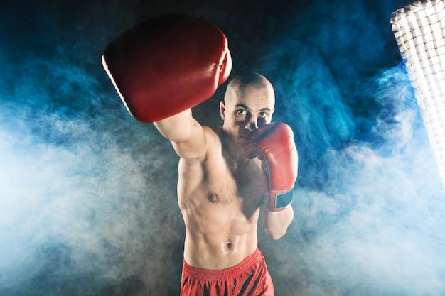 Joven kickboxing en humo azul Foto gratis
