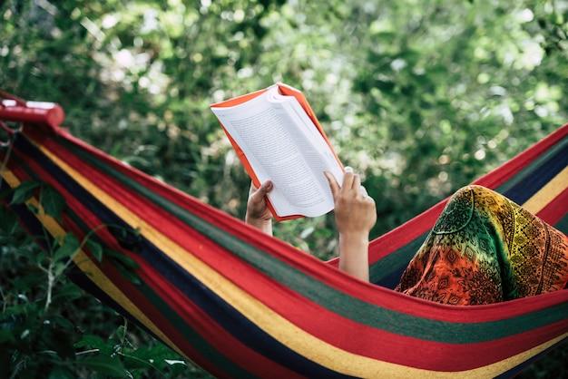 Joven leyendo un libro acostado en una hamaca Foto gratis