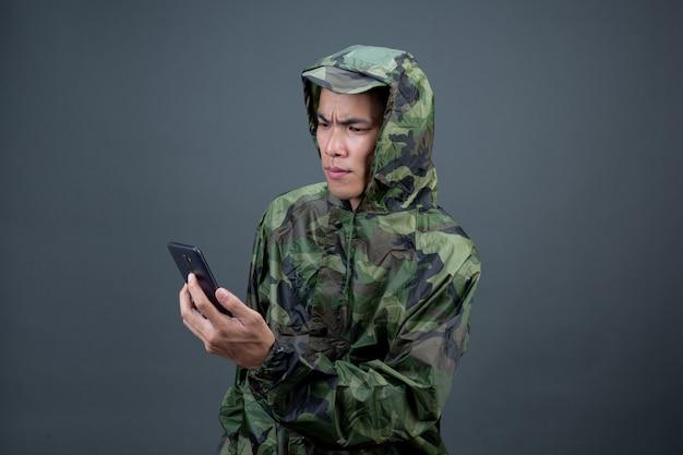 El joven lleva un impermeable de camuflaje y muestra diferentes gestos. Foto gratis
