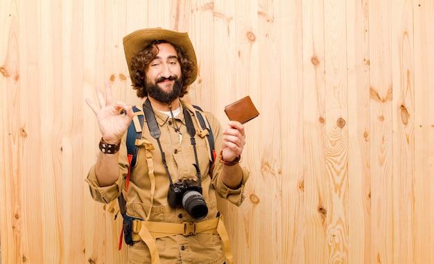 Joven loco explorador con sombrero de paja y mochila sobre fondo de madera Foto Premium