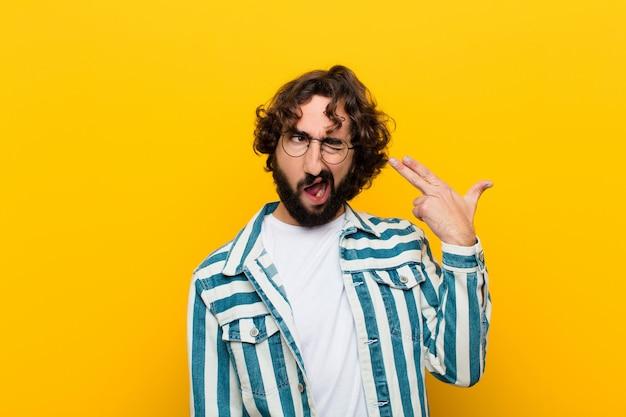 Joven loco que parece infeliz y estresado, gesto de suicidio haciendo signo de arma con la mano, apuntando a la cabeza pared amarilla Foto Premium