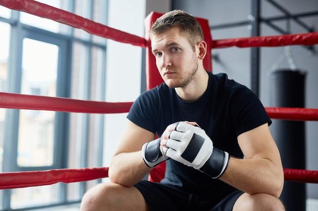 Joven luchador sentado en el ring de boxeo Foto gratis