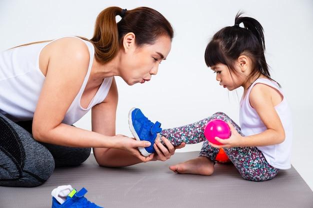 Joven madre ayuda a linda hija con zapatos Foto gratis