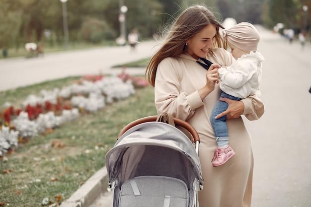 Joven madre caminando en un parque de otoño con carro Foto gratis