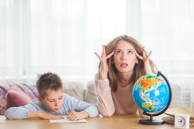 Foto Premium | Joven madre enseñando a su pequeño hijo en casa. mamá y su hijo estudian geografía en interiores