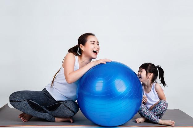 Joven madre con hija pequeña ejercicio en pelota fitness Foto gratis