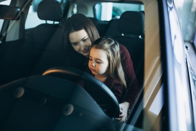 Joven madre con hija pequeña sentada dentro de un automóvil Foto gratis