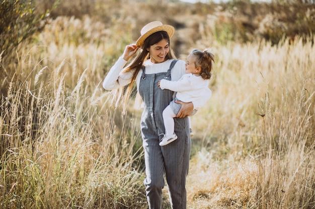 Joven madre con su pequeña hija en un campo de otoño Foto gratis