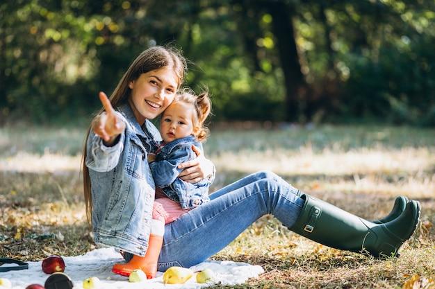 Joven madre con su pequeña hija en un parque de otoño con picnic Foto gratis