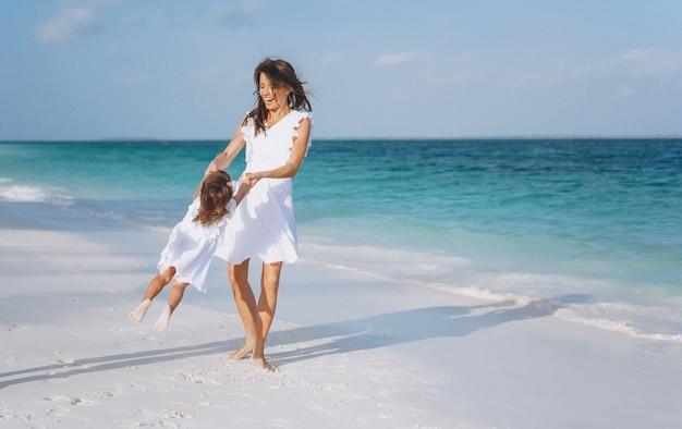 Joven madre con su pequeña hija en la playa junto al mar Foto gratis