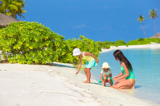 Joven madre y sus dos hijas en la playa exótica en un día soleado Foto Premium