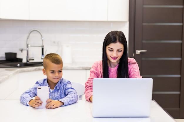 Joven madre trabajando en la computadora portátil en casa, mientras que su hijo está aburrido de jugar en el teléfono Foto gratis