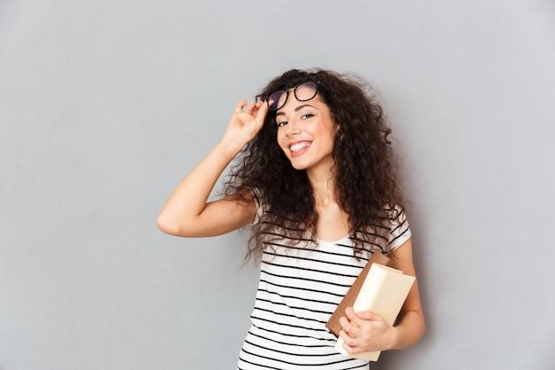 Joven maestra en anteojos con cabello rizado de pie con libros en mano sobre pared gris disfrutando de su trabajo en la universidad siendo inteligente e intelectual Foto gratis