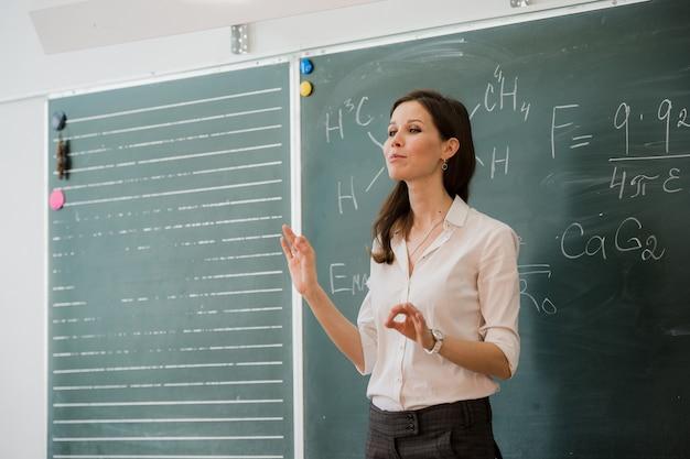Joven maestra feliz hablando con clase de pie contra el tablero verde Foto Premium