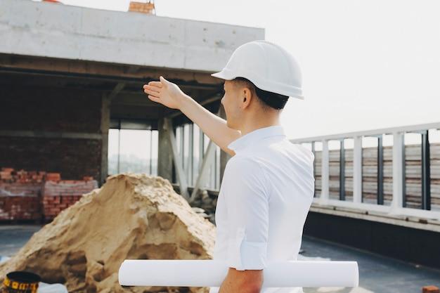 Joven maestro mostrando dónde hacer cambios de edificio en construcción. Foto Premium