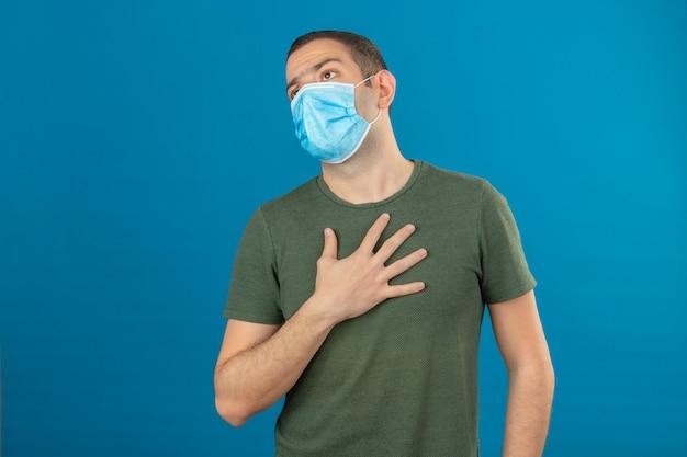 Joven con máscara médica cara difícil de respirar mientras toca su pecho con la mano aislada en azul Foto gratis